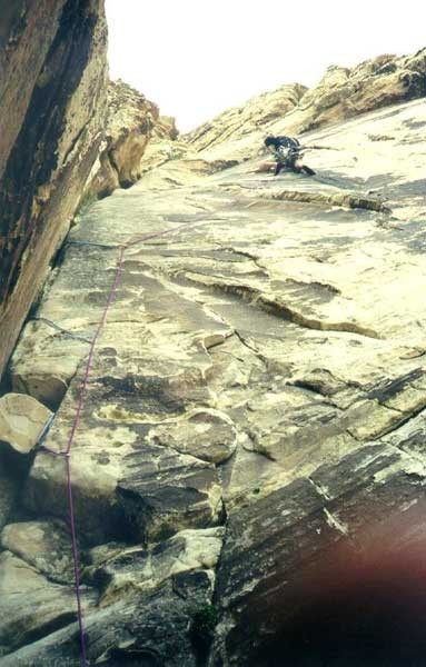 Looking up at a climber on pitch 6.