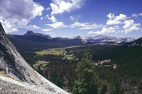 A climber on Crying Time Again on Lembert Dome; Cathedral Pk. can be s...