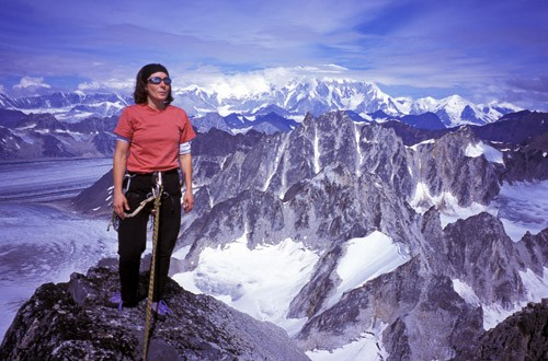 Michelle Puryear on the summit ridge of the Throne with Mt. Foraker in...