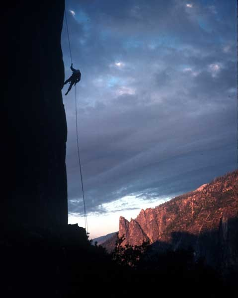 Tom Frost rappelling from Lower Cathedral Spire at sunset.