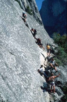 Many soloists passing a party on Royal Arches with Half Dome in the ba...