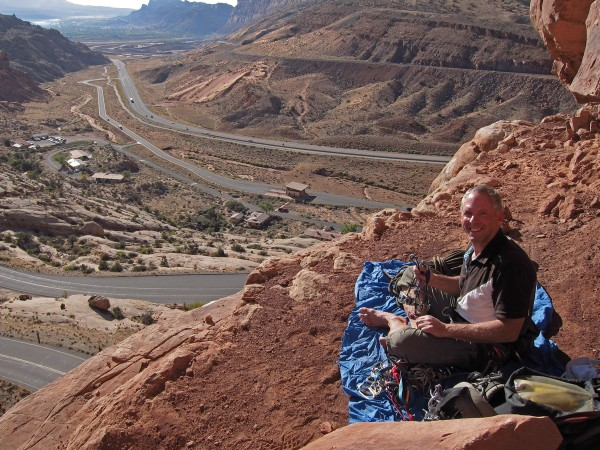 Racking up at the base of the 3 Penguins, Moab in the distance.  A sem...