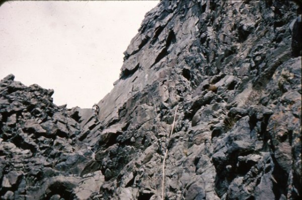 Climbing up the black chossy rock on the west side to a notch.