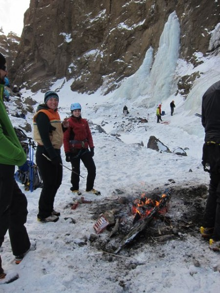 Climbers practice on the line of ice, while bystanders cook hot dogs.
