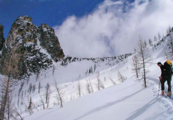 Kurt Hicks approaching the Southwest Couloir under typical early seaso...