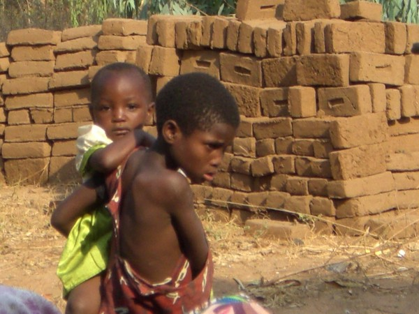 Orphan children with hand made bricks in the background.  Gogos have b...