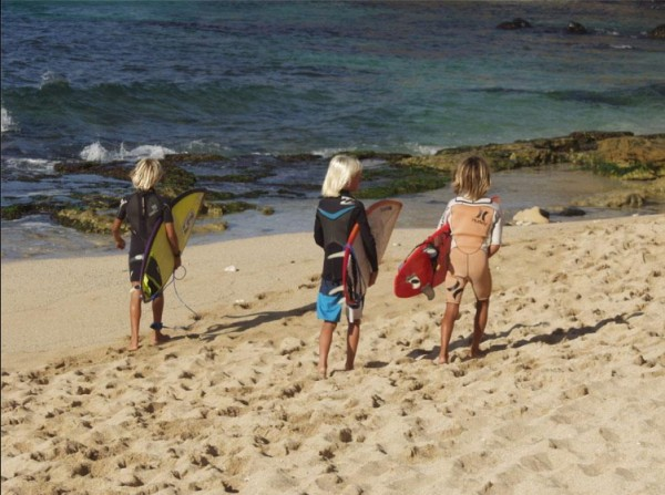 Axel Rosenblat and two of his grom pals about to paddle out at Hookipa
