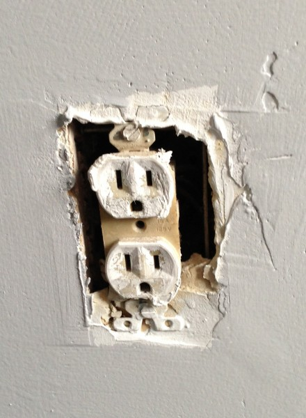 Old outlet covered with paint and junk from previous owner