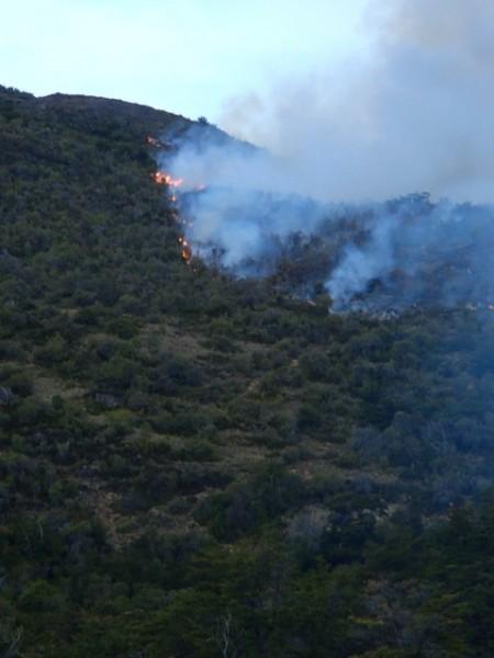 Fire still burning on hillside above house.