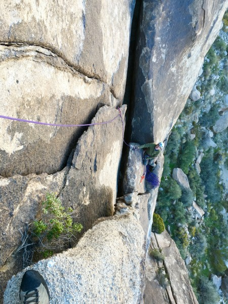 Looking down at David Foss belaying from the top of pitch one of Mache...