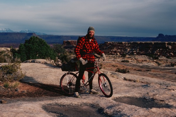 Steve and his bike on the Permian White Rim Sandstone Formation.  Not ...