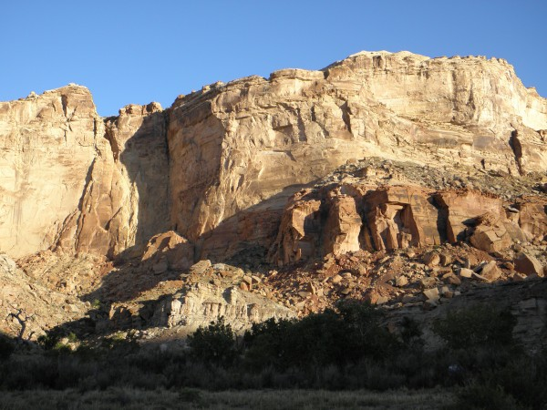 The cliffs of the Glen Canyon Group soar over the bottom lands at Toms...