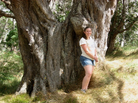 Briana on her 16th B-Day, standing next to a large native Koa tree.