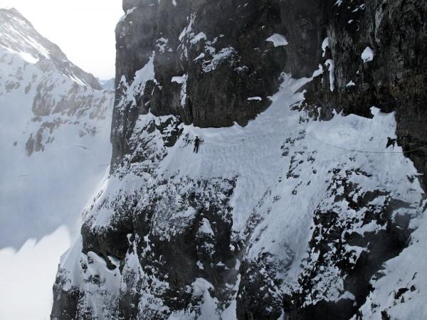 Alik Berg shuffles across a steep ledge of snow-covered choss halfway ...
