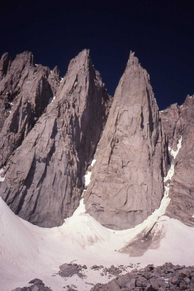 There are 3 people on the snow below the toe of Day Needle.